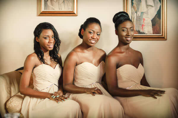Three bridesmaids seated on a bench in a classic pose