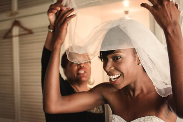 Veil being lifted over bride's face as she gets ready