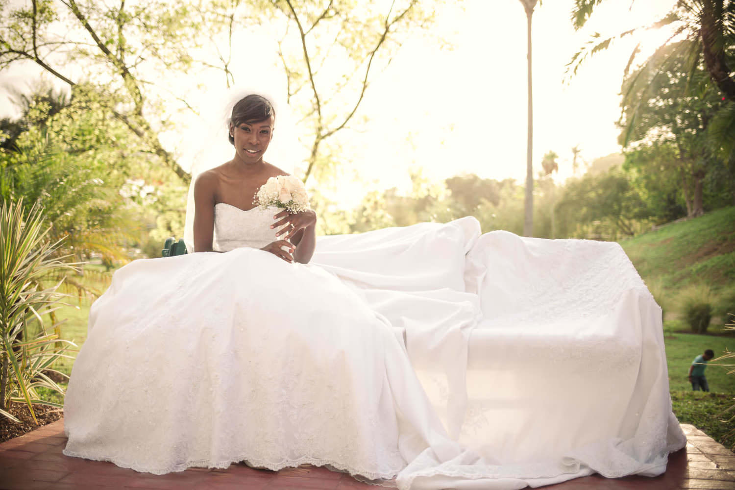 Bride sits with dress covering bench in park backlit by the golden sun