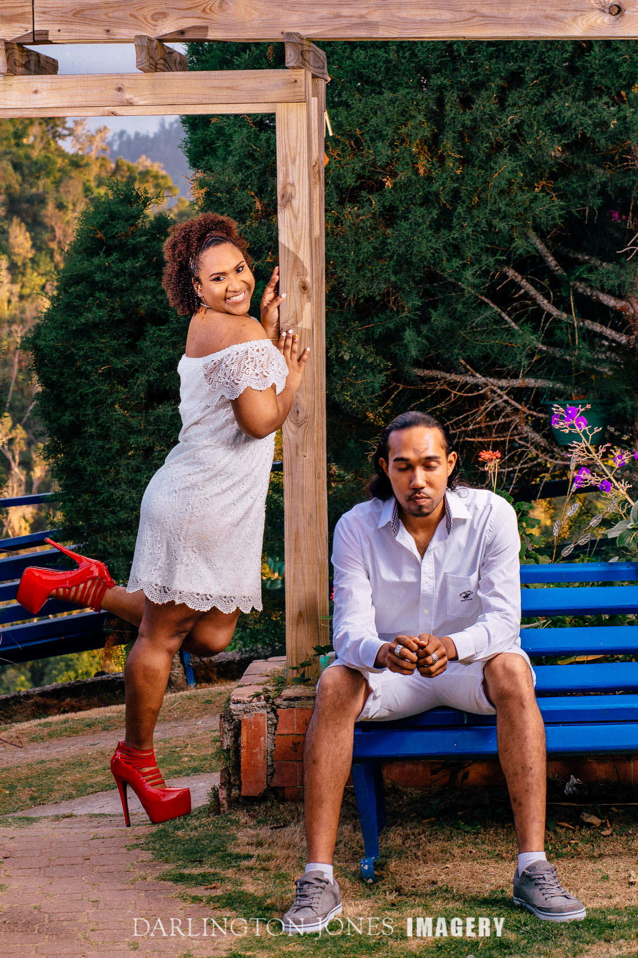 Engaged Couple Man Sitting on Blue Bench Lady in Red Shoes Standing